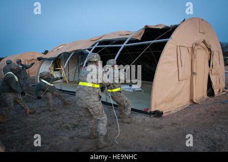 Airmen from the Kentucky Air National Guard's 123rd Contingency Response Group set up an Alaskan Shelter tent at - Stock Photo