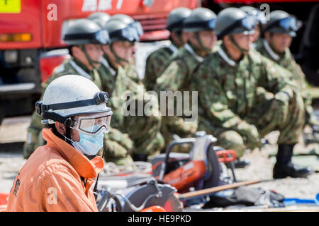 An Okinawa emergency responder waits alongside Japan Ground Self-Defense Force members before clearing rubble to - Stock Photo