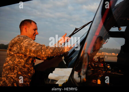 U.S. Army Sgt. Matthew Larsen, 7th Battalion, 158th Aviation Regiment, cleans the windows of a UH-60 Blackhawk while - Stock Photo