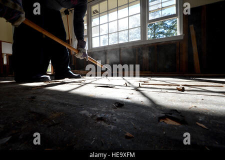 A disaster relief volunteer uses a roofing shovel to remove wood flooring during a disaster relief effort to assist - Stock Photo