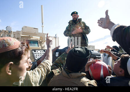 Afghan National Army soldiers distribute soccer balls and air pumps to villagers at Tandan Village, Afghanistan, - Stock Photo