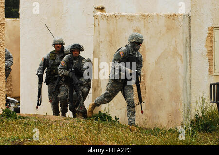 U.S. Army soldiers assigned to the 83rd Military Police Company move to assault positions while defending against - Stock Photo