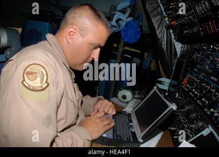 Tech. Sgt. Jeff Seren works with takeoff and landing data in the cockpit of a C-5 Galaxy cargo aircraft at Joint - Stock Photo