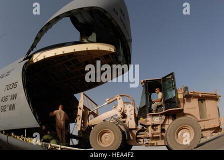 Staff Sgt. Jeffrey Szymanski (right) loads a jet engine aboard a C-5 Galaxy at Joint Base Balad, Iraq, Sept. 26, - Stock Photo