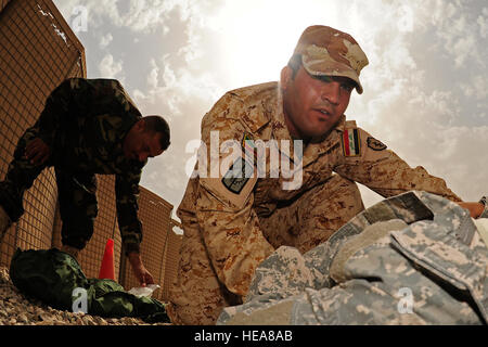 An Iraqi soldier from the 4th Iraqi Army Engineer Regiment, performs an evaluation on a mock casualty while U.S. - Stock Photo