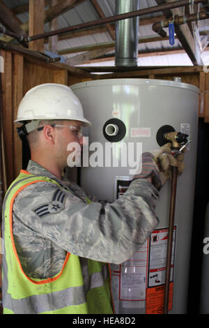 Senior Airman Derek Reeves tightens a fitting on a new hot water tank installed at Camp Hind Boy Scout Camp, Raymond, - Stock Photo
