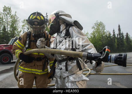 U.S. Air Force fire protection specialists assigned to the 673rd Civil Engineer Squadron confer with each other - Stock Photo