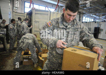 Army Staff Sgt. Barry Joyce, a native of Martinsville, Va., tapes a box to load batteries in as fellow soldiers - Stock Photo