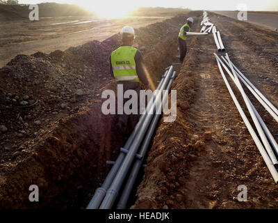 Contractors install conduit lines at Kirkuk Regional Air Base, Iraq, as part of a foreign military sales effort - Stock Photo