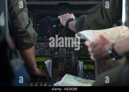 U.S. Air Force pilots assigned to the 517th Airlift Squadron handle controls and maps during a low-level flight - Stock Photo