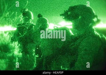 Marines set up a security perimeter after moving to a simulated enemy compound during a night raid training evolution - Stock Photo