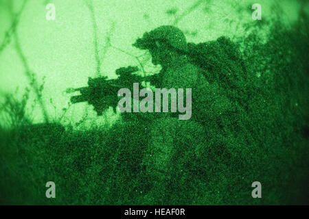 A Marine scouts a simulated enemy compound for hostile activity during a night raid training evolution aboard Marine - Stock Photo