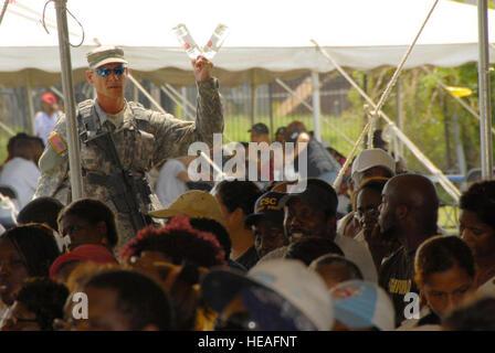 Louisiana Army National Guardsman Pvt. Cody Crader of A Company, 3rd Battalion, 156th Brigade distributes water - Stock Photo