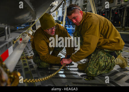 Petty Officer 2nd Class Matthew Farr (right), a machinery technician stationed at Port Security Unit 309 in Port - Stock Photo