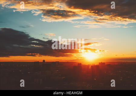 Dramatic red scenery of city silhouette at sunset with strong sun flare, teal sky with clouds and rays of light - Stock Photo