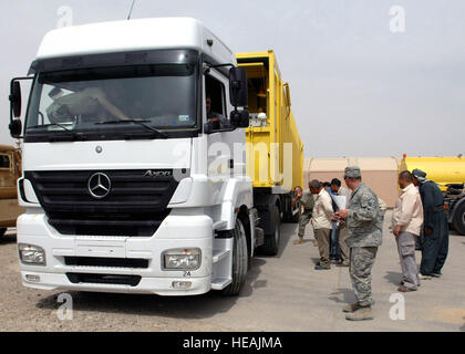 An Iraqi takes the helm of a new truck purchased by coalition forces to help improve waste management practices - Stock Photo