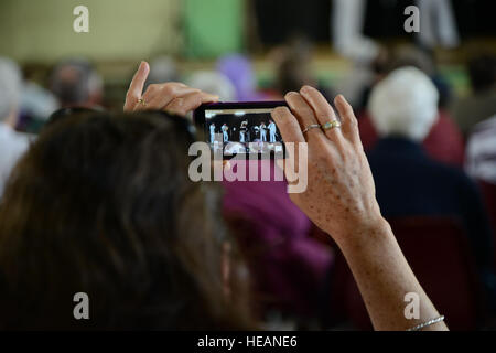 An audience member records the Pacific Ambassadors, a division of the U.S. 7th Fleet Navy Band, during a concert - Stock Photo