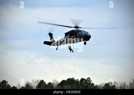 A UH-60 Black Hawk lifts a Charlotte fire fighter during rescue training over the Salisbury Army Guard flight facility - Stock Photo