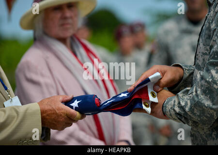 French locals and U.S. Soldiers from the Fort Bragg Air Assault School, N.C., fold an U.S. flag during a memorial - Stock Photo
