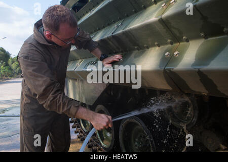 U.S. Marine Corps Lance Cpl. Kendrick Helms washes the mud from under the tracks of an AAV-P7/A1 Amphibious Assault - Stock Photo