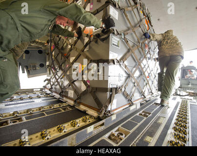 U.S. Air Force Master Sgt. Michelle Hite (left), 326th Airlift Squadron, offloads cargo from  a C-17 Globemaster - Stock Photo