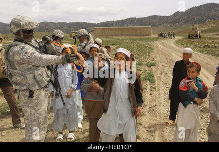 PAKTIKA PROVINCE, Afghanistan – U.S. Army Sgt. Terrance Ray receives a sling-shot lesson from local children while - Stock Photo