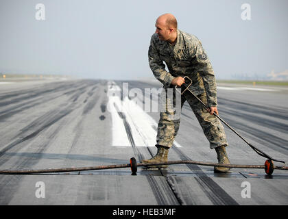Tech. Sgt. Brian Brown, 354th Civil Engineer Squadron power production NCO in charge, drags a cable into place in - Stock Photo