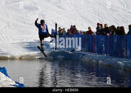 Ken Donnolly skis into a man-made pool of water during the Slush Cup on Joint Base Elmendorf-Richardson, Alaska, - Stock Photo