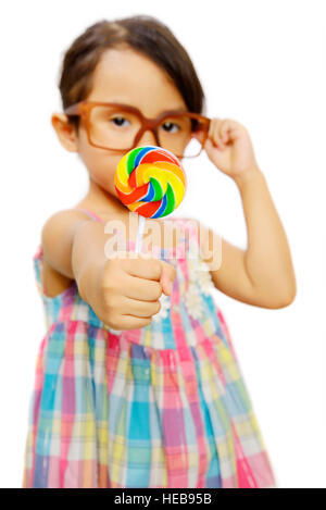 Cute little girl wearing glasses eating her lollipop isolated over white background - Stock Photo