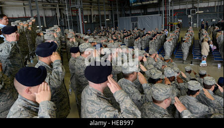 Airmen salute while the base honor guard posts the colors during the 86th Airlift Wing change of command ceremony - Stock Photo