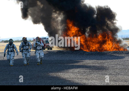 Members of the 355th Civil Engineer Squadron's fire department walk away from a fire on the fire training grounds - Stock Photo