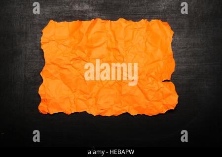 Orange burnt paper on chalkboard. You can put your design on the paper - Stock Photo