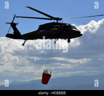A UH-60 Black Hawk helicopter assigned to Joint Task Force-Bravo's 1-228th Aviation Regiment carries a Bambi Bucket, - Stock Photo
