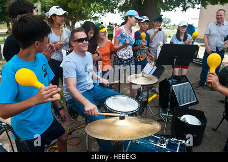 Senior Airman Simon Thomsen plays the drums for Kyrgyz Republic children after the U.S. Air Forces Central Band - Stock Photo