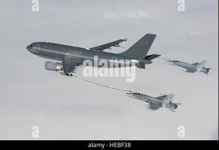 A CC-150 Polaris Airbus from 437 Squadron in Trenton provides air-to-air refueling to CF-18 Hornet fighter aircraft - Stock Photo