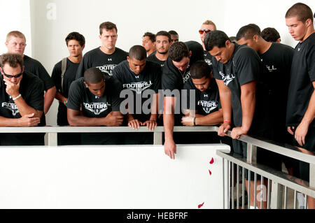 University of Hawaii football players drop flower petals into the water to honor the men entombed in the USS Arizona - Stock Photo