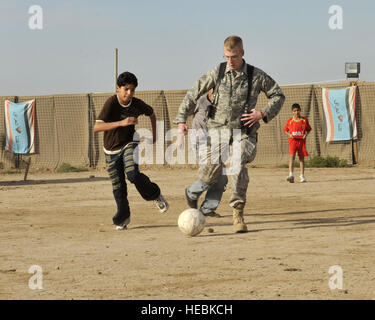 Staff Sgt. Dustin Groves plays socker with a Iraqi children at a secure compound in Baghdad Dec 19. Sergeant Groves - Stock Photo