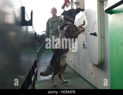U.S. Navy Petty Officer 2nd Class Michael Carter, a military working dog handler assigned to Camp Lemonnier, and - Stock Photo