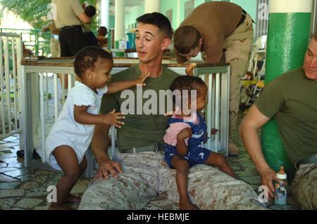 DJIBOUTI – During a visit to the Djibouti baby orphanage, Marine 1st Lt. Tim J. Lockhart spends time with children - Stock Photo