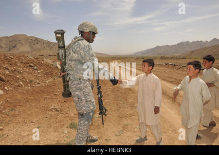 Pfc. Jessie Bell, Ghazni Provincial Reconstruction Team security forces member, shakes hands with an Afghan boy, - Stock Photo
