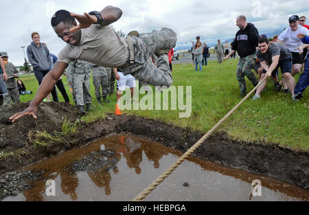 Senior Airman Ricky Jones screams as he leaps over a mud pit in an effort to avoid being submerged in muddy water - Stock Photo