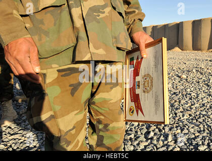 An Afghan national army soldier stands at attention while holding his certificate of completion during the Task - Stock Photo