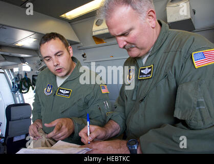 Tech. Sgt. Brandon Heyman (left) and Master Sgt. Corbet Cadwell sign off on accepting flight meals before the takeoff - Stock Photo