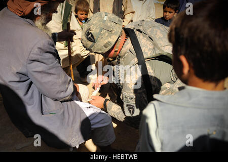 An Afghan boy looks on as U.S. Army Spc. John Alred, Texas Agribusiness Development Team-04 medic, performs a medical - Stock Photo