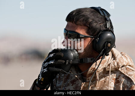United Arab Emirates Sgt. Maj. Abdul Alkalar, a crew chief assigned to the Saheen 3 Squadron, uses a head set to - Stock Photo