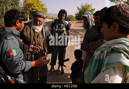 Members of the Afghan National Police speak to local villagers about the upcoming parliamentary elections in Afghanistan - Stock Photo