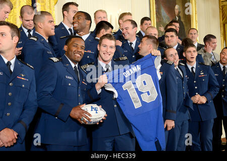 Members of the U.S. Air Force Academy football team stand with the jersey and football they intend to present to - Stock Photo