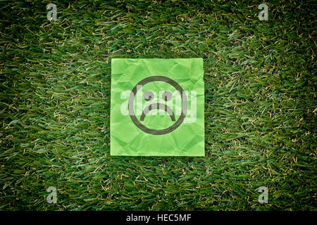 Green paper with sad unhappy face on a green grass. Close up. - Stock Photo