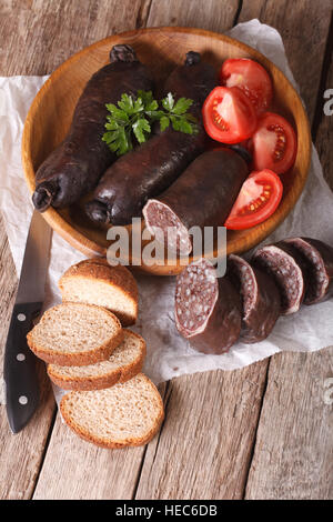 Delicious blood sausages and vegetables on a table close-up. Vertical - Stock Photo