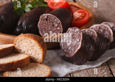 Fresh blood sausages and vegetables on a wooden plate close-up. horizontal - Stock Photo